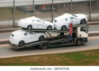 Delivery truck trailer transports three cars on the highway