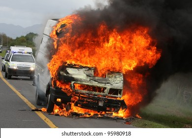 Delivery type vehicle on side of road burning with large flames and smoke and police cars in background