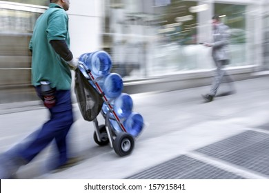 delivery water with dolly by hand, purposely motion blur