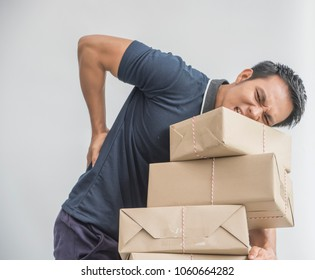 Delivery Worker  lifting  heavy weight boxes  against  having a backache
