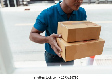 Delivery worker in uniform carrying packed box with supplies standing infront of the house waiting for customer to receive them.