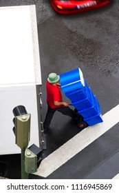 delivery  worker  with wheelbarrow unloading boxes from a truck
