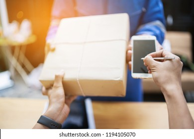 Delivery,mail and shipping,delivery man Checking Portable Device with Asian woman sign in digital Smartphone before receiving parcel or receive package,she appending signature in mobile phone at home.