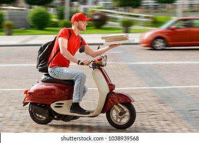 Deliveryman driving through the city on a motorbike. Happy man is carrying pizza boxes, delivering to customers.