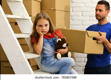 Deliveryman and girl with sad or bored face. Dad and daughter by pile of cardboard boxes and white ladder. Man holds box and kid has bear on light room background. Moving in and family problem concept