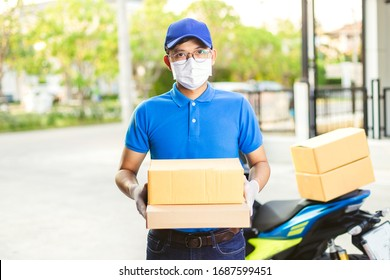 Deliveryman of goods and parcels to customers by protecting them with medical masks and gloves / Online shopping order under quarantine coronavirus covid-19