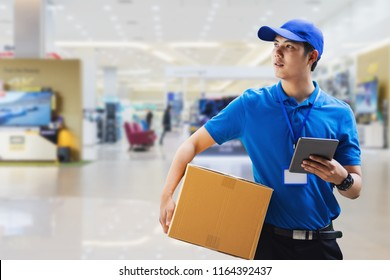 deliveryman holding box and using digital tablet