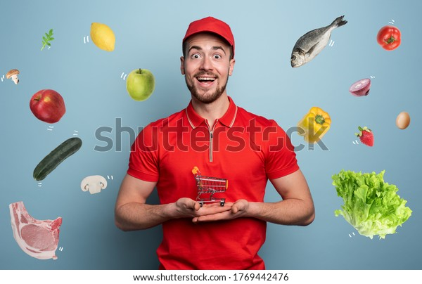 Deliveryman holds a small cart that is filled with food. Cyan background.