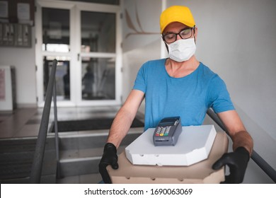 Deliveryman with protective medical mask holding pizza box - days of viruses and pandemic, food delivery to your home.