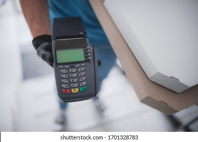 Deliveryman with protective medical mask holding pizza box and POS wireless terminal for card paying - days of viruses and pandemic, food delivery to your home.