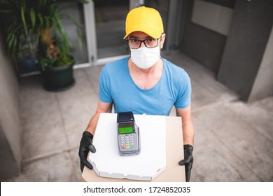 Deliveryman with protective medical mask holding pizza box and POS wireless terminal for card paying - days of viruses and pandemic, food delivery to your home and safety hygiene measures.