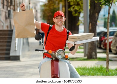 Deliveryman is showing food package, holding a parcel and boxes. Man enjoys his work in the delivery service.