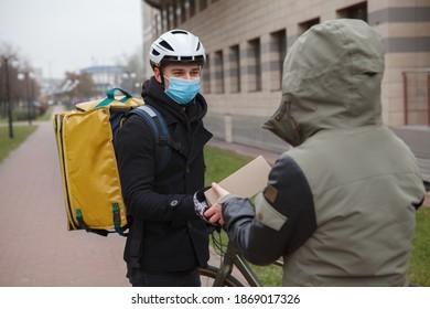 Deliveryman wearing medical mask delivering cardboard box to a customer, wearing medical face mask during coronavirus quarantine