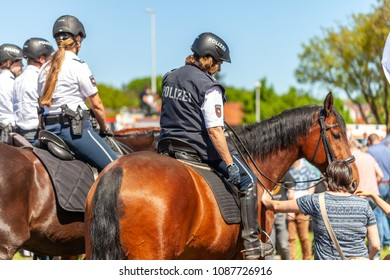 DELMENHORST / GERMANY - MAY 6, 2018: German police horsewoman rides on a police horse for training exercise in a crowd. The german word Polizei means police.