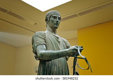 DELPHI, GREECE - APRIL 17, 2009: Upper half of the Heniokhos charioteer bronze statue at the archaeological museum of Delphi. One of few bronze statues to retain the inlaid glass eyes.