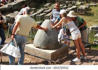 DELPHI, GREECE - SEPTEMBER 19, 2012: Unknown tourists traditionally make a wish on the stone, which symbolizes the Navel of the Earth.