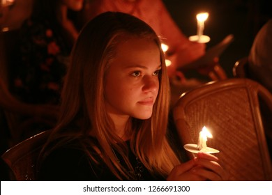 DELRAY BEACH, FLORIDA / USA - DECEMBER 24 2018:  Closeup of a girl holding a lit candle honoring the birth of Jesus Christ in Unity Church on Christmas eve.