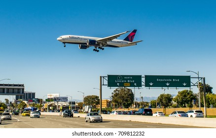 A Delta Air Lines Boeing 777 flies over the Pacific Coast Highway moments before touchdown onto Runway 27R at Los Angeles International Airport (LAX) on May 21, 2017