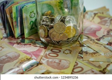 Delta, British Columbia / Canada - November 3rd 2018 - A Jar and Pile of Canadian Cash