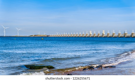 The Delta Works Storm Surge Barrier and Wind Turbines at the Oosterschelde viewed from Banjjardstrand in Zeeand Province in the Netherlands