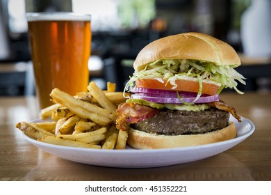 Deluxe Hamburger with Lettuce, Onion, and Tomato Served with French Fries and a Cold Beer