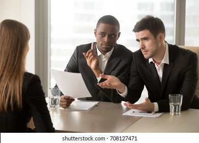 Demanding multinational recruiters meticulously examining female job candidate with asking difficult questions. Woman giving wrong or bad answers on job interview. Applicant questionable qualification