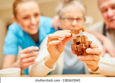 Demented senior woman puts blocks of wood together in the nursing home as a patience game