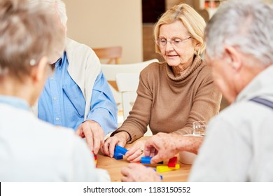 Demented seniors in retirement home play with colorful building blocks as employment
