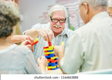 Dementia group in retirement home plays together with building blocks as therapy