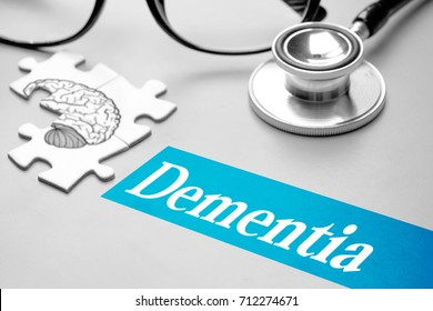 Dementia, medical concept. Puzzle with brain, eye glass and stethoscope on grey background. Selective focus image.
