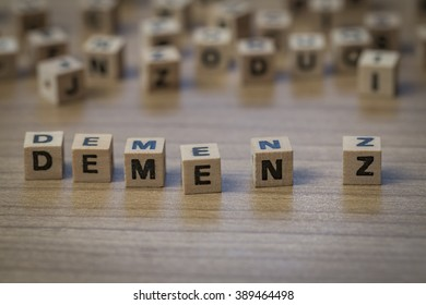 Demenz (German Dementia) written in wooden cubes on a table from well ordered to chaotic