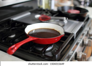 Demi-glace cooked in a coated enamel skillet on the stove top in a home kitchen.