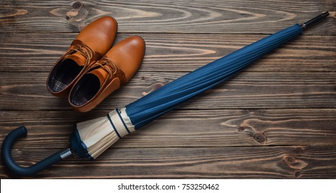 Demi-season leather half-boots and a folded umbrella on a wooden floor. Top view. Waxing women's accessories for rainy weather.