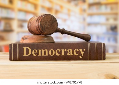 democracy law books and a judge gavel on desk in the library. concept of democracy education.