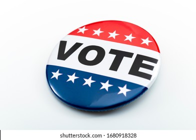 Democracy, presidential election and voting poll concept with red, white and blue vote glossy button pin with stars and stripes isolated on white background with clipping path cutout