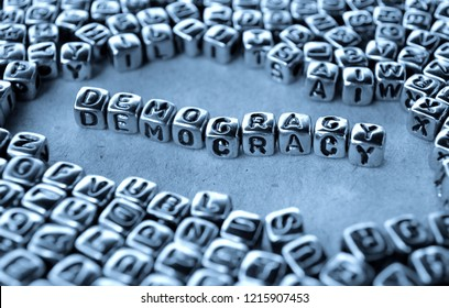 Democracy - Word from Metal Blocks on Paper - Concept Photo on Table