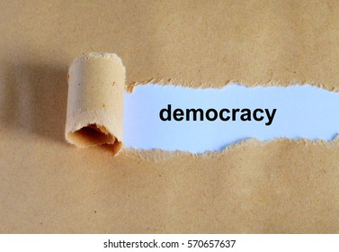 Democracy word written under ripped and torn paper.