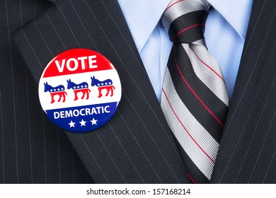 A democratic voter proudly wears his party badge on his suit lapel