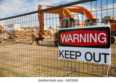 Demolished building, with a keep out sign on the fence.