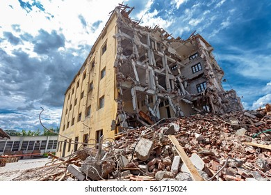 Demolished building surrounded with rubble and scrap. Deconstruction of building. Earthquake ruin scene. Destruction concept.