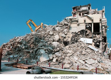 Demolishing a building in the city. Excavator is demolishing concrete walls.