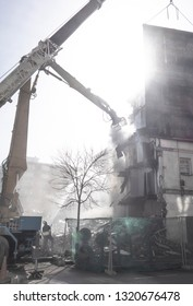 demolition of a building with a backhoe  or demolition of a building with a big crane or demolition works with a lot of dust and watering the debris,