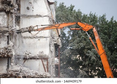 Demolition of building. Red grab crane with hydraulic scissors closeup, side view. Reinforced concrete structures.