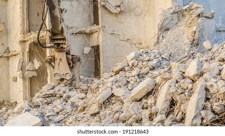 Demolition crane jaw head with debris and rubble in evening