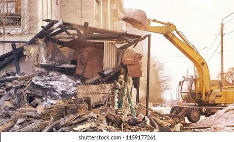 Demolition house using excavator in city. Rebuilding process. Remove equipment.