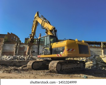 Demolition house using excavator in city. Rebuilding process. Remove equipment.