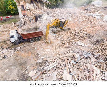 demolition of an old building. hydraulic excavator and dump truck clearing out debris and garbage