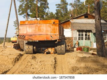 Demolition of the old house. Bulldozer near dilapidated.