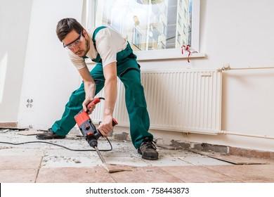 Demolition of old tiles with jackhammer. Renovation of old floor.
