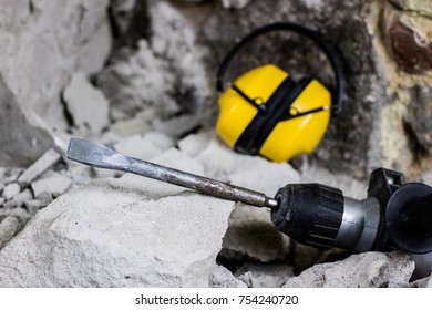 Demolition of walls. Electric hammer helmet and hearing protection lying on the rubble. Old brick and remodeled building wall. Grunt on the background of the old wall.